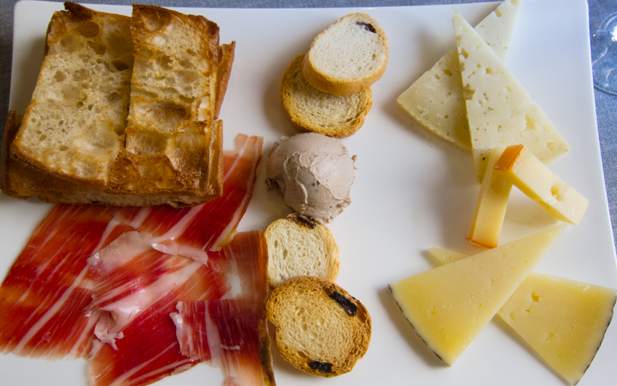 Cheese and Spanish ham served on a plate for sharing